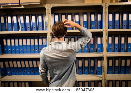 Rear view of confused businessman searching for files on cabinet in storage room