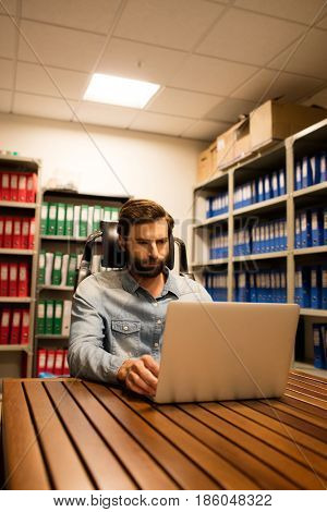 Business executive using laptop on table in file storage room