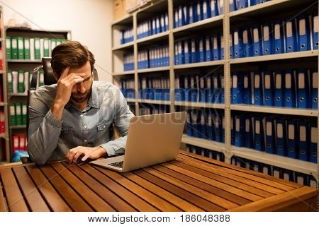 Tensed business executive using laptop on table in file storage room