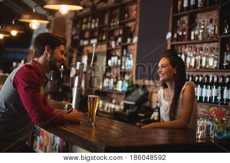 Female bar tender interacting with customer at bar counter poster
