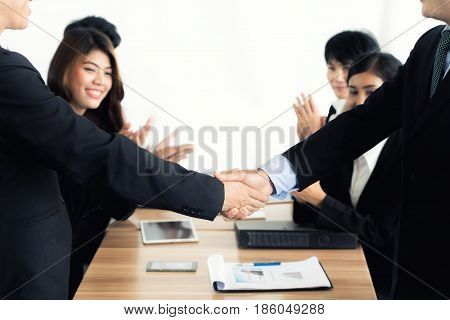 Asian businessman shaking hands in conference room. Business people shaking hands agreement concept.