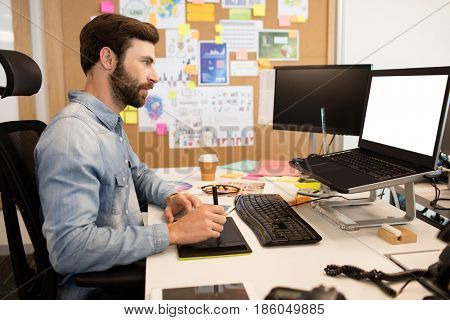Side view of designer using digitizer and stylus on creative office desk