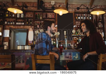 Friends having beer at bar counter in pub