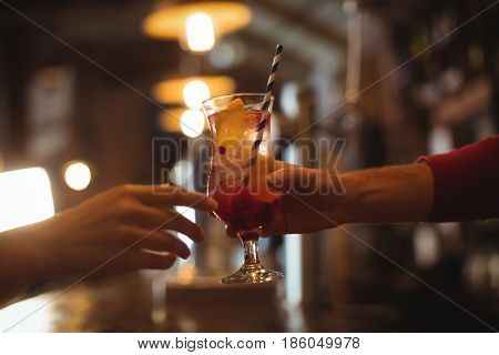 Close-up of female bar tender giving glass of cocktail to customer at bar counter