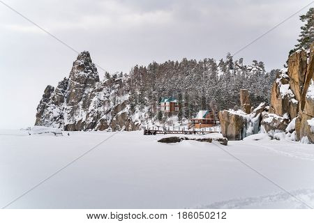 View of snow mountain and a village in Frozen Lake Baikal during snow fall