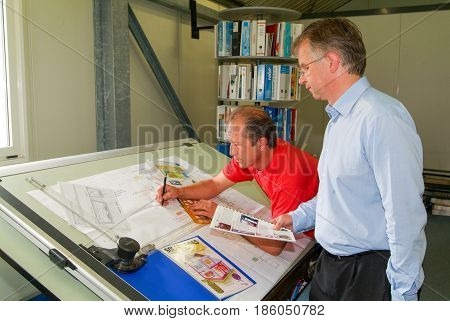 Engineers Working Together At Drawing Board On Them Office