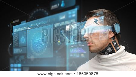 augmented reality, technology, business, future and people concept - man in virtual glasses and microchip implant or sensors looking at screen projections over dark background