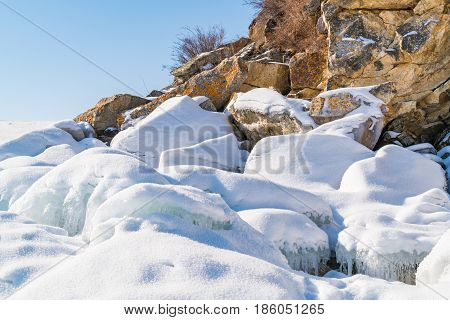 Frozen water and rocks covered with snow at rocky island in Lake Baikal Russia during winter