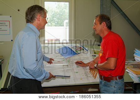Bellinzona Switzerland - 3 June 2005: Engineers working together at drawing board on them office