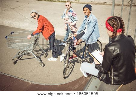 Teenagers Having Fun With Shopping Cart And Bicycle In Skateboard Park, Hipster Style Concept