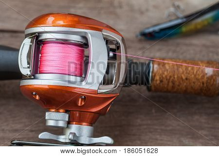 Fishing tackle - Baitcasting Reel hooks and lures on wooden background
