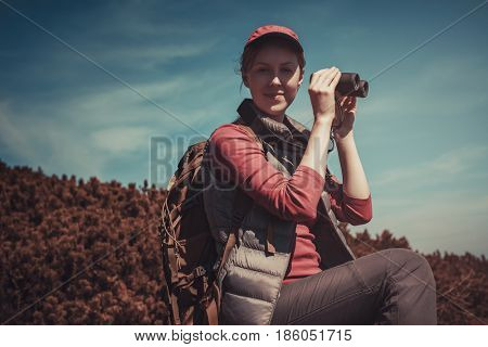 Young woman tourist with binoculars portrait. Film style autumn colors.