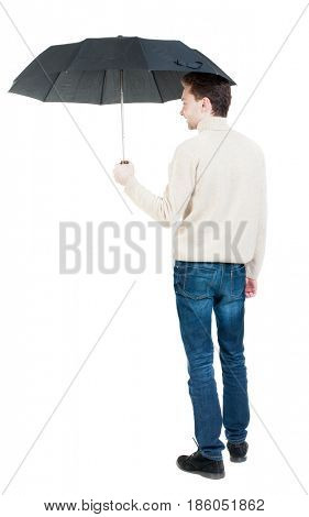 Back view of man in jeans under an umbrella. Standing young guy. Rear view people collection.  . A guy in a white warm sweater hiding from the rain under an umbrella, and someone...