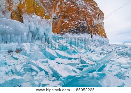 Blue frozen water covered with snow and icicles at rocky island in Lake Baikal Russia