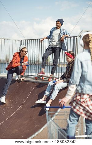 Teenagers group having fun together on ramp at skateboard park