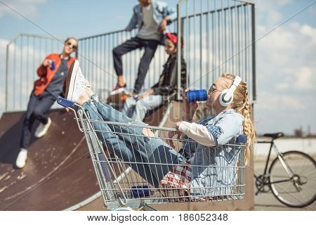 Girl in headphones sitting in shopping cart and drinking from can while friends having fun on ramp at skatepark