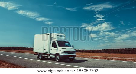 Light truck travel on europe road. Blue sky and autumn field panorama.