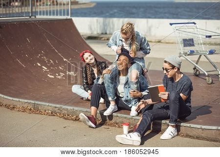 Teenagers Group Sitting Together On The Ramp And Having Fun At Skateboard Park