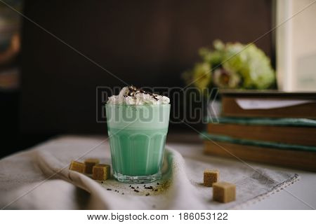 Green mint coffee with with cream and colorful decoration on dark background. Milk shake cocktaill frappuccino. Unicorn coffee unicorn food.