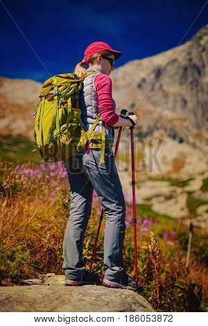 Young woman tourist with green backpack and sunglasses standing on high mountains background