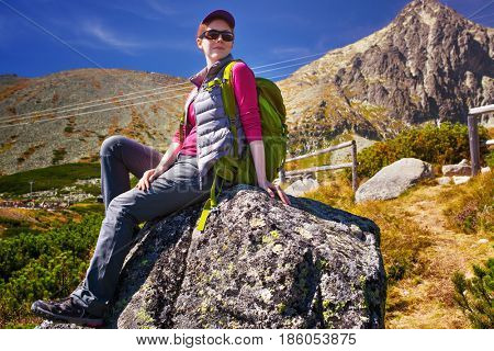 Young woman tourist with green backpack and sunglasses sitting on high mountains background