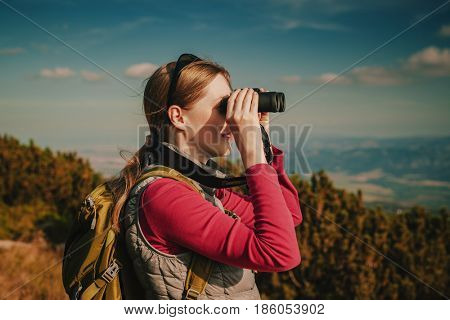 Young woman tourist with binoculars looking on mountains
