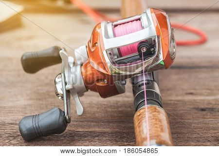 Fishing tackle - Bait casting Reel on wooden background