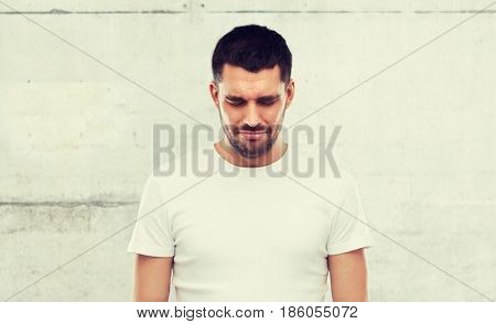 emotion, sadness and people concept - unhappy young man over gray wall background
