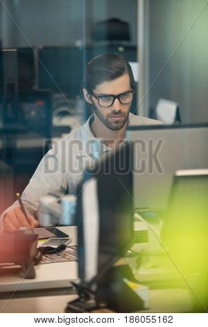Concentrated businessman working on digitizer at desk in office