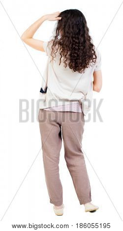 back view of standing young beautiful  woman.  girl  watching. Rear view people collection.  backside view of person. girl with curly hair looking palm covering eyes from the sun.