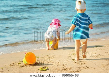 Babygirl and babyboy palying on the beach in summer
