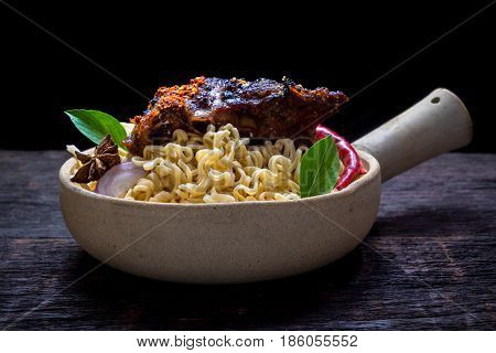 Instant noodles with roast pork spareribs in the clay pot on wooden background