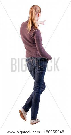 Back view of  pointing woman. beautiful blonde  girl in jeans. girl in a sweater and sandals considering something far. long-haired teen girl pokes his finger somewhere