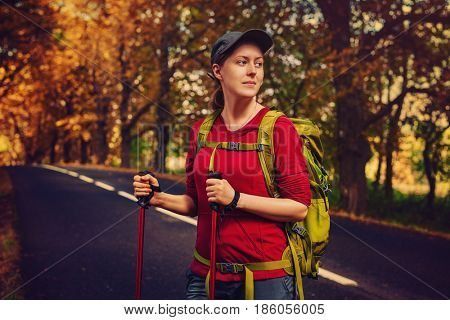 Young woman tourist walking with sticks and backpack on road. Warm sunset colors.