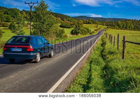 Old car traveling on Europe country landscape with field and forest