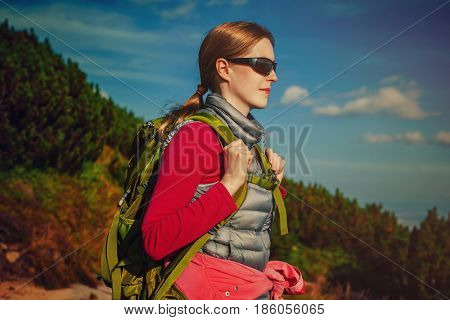 Young woman tourist with green backpack and sunglasses standing on mountains background