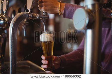 Close-up of bar tender filling beer from beer pump at bar counter