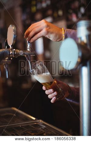 Close-up of bar tender filling beer from bar pump at bar counter