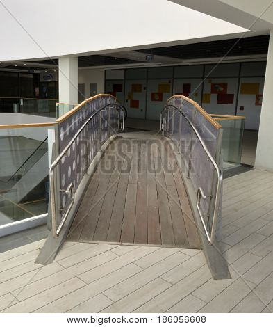 Transition bridge connecting galleries with a glass parapet handrails of stainless steel pipes floor of planks