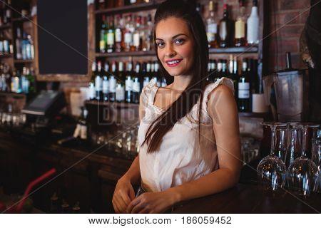 Portrait of female bartender standing at bar counter