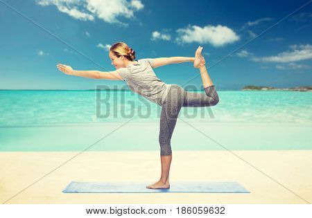 fitness, sport, people and healthy lifestyle concept - woman making yoga in lord of the dance pose on mat over beach background