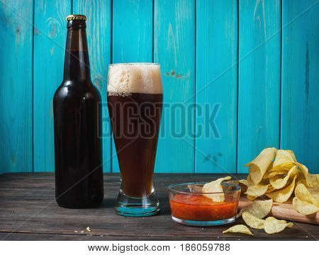 glass and bottle of dark beer with crumbs of chips on wooden table. Mockup