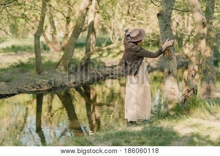 in the woods near the river in the sun posing a woman in a long dress and hat