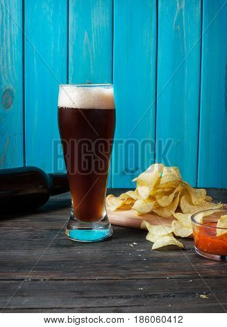 glass and bottle of dark beer with crumbs of chips on wooden table.