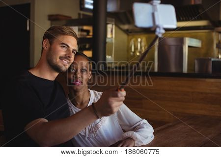 Couple taking selfie from mobile phone in restaurant