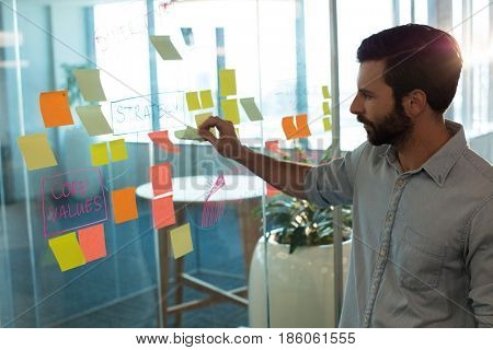 Businessman analyzing adhesive notes on glass at office