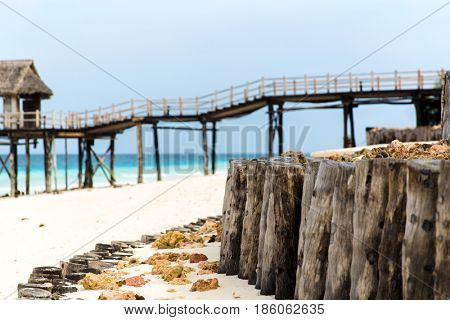 travel, tourism, vacation and summer holidays concept - bridge to bungalow hut or stilt house on tropical resort beach