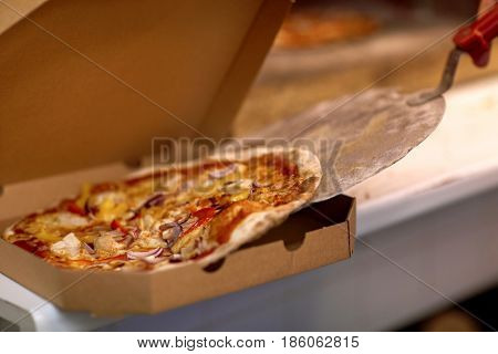 food, italian cuisine, culinary and cooking concept - chef placing pizza from peel to cardboard box at pizzeria