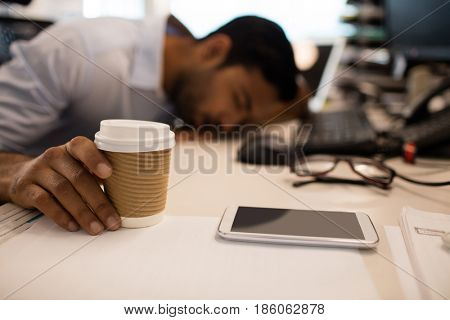 Businessman sleeping while holding disposable coffee up on desk at office