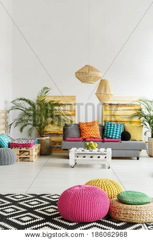 Trendy living room with colorful poufs and grey couch